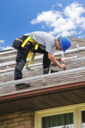 woonwijk: Man rails voor zonne panelen installeren op woonhuis dak