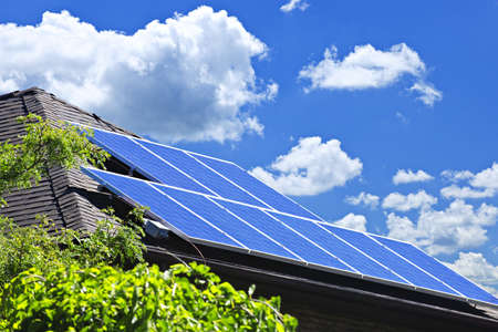 electric grid: Array of alternative energy photovoltaic solar panels on roof of residential house