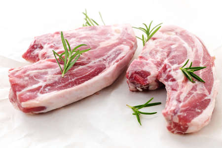 Two raw fresh lamb chops with rosemary herb