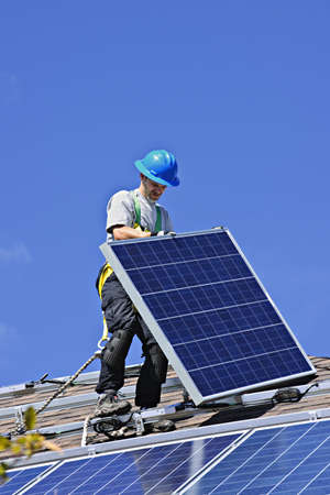 代替エネルギー太陽光発電太陽電池パネルをインストールする屋根の上の男