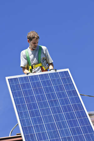 Man installing alternative energy photovoltaic solar panels on roof photo