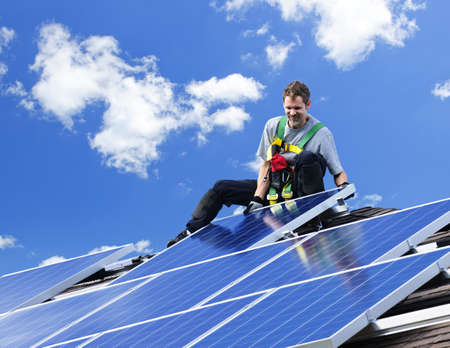 panel: Worker installing alternative energy photovoltaic solar panels on roof