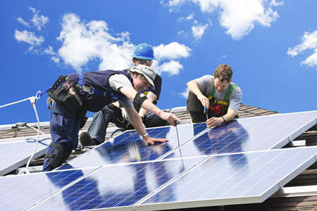 Workers installing alternative energy photovoltaic solar panels on roof photo
