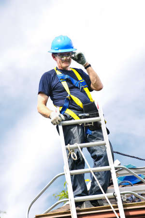 Construction worker standing on roof near ladder