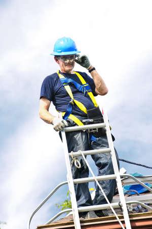 rungs: Trabajador de la construcci�n permanente de techo cerca de escalera