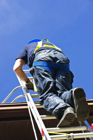Construction worker climbing extension ladder to roof photo