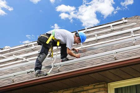 Man installing rails for solar panels on residential house roof Stock Photo - 7983267