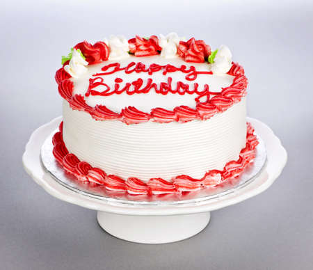 vanilla cake: Birthday cake with white and red icing on plate