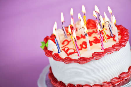 Birthday cake with burning candles on a plate on pink background Фото со стока