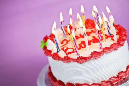 gateau anniversaire: G�teau d'anniversaire avec bougies allum�es sur une plaque sur fond rose Banque d'images