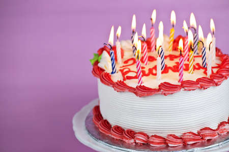 candle: Birthday cake with burning candles on a plate on pink background Stock Photo