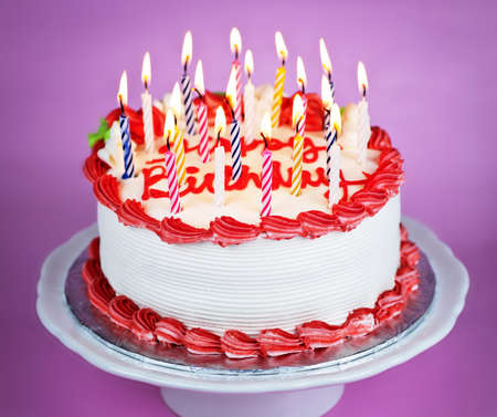 Birthday cake with burning candles on a plate on pink background 版權商用圖片 - 7996139
