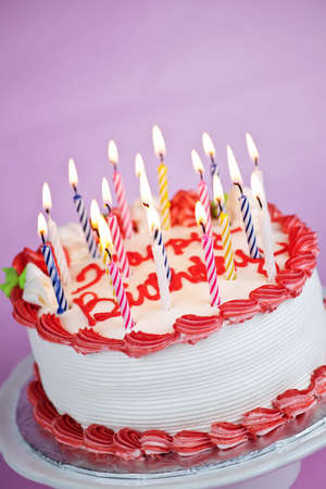 Birthday cake with burning candles on a plate on pink background Stockfoto