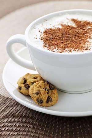 galleta de chocolate: Cappuccino o latte caf� en la taza con leche espumada y cookies