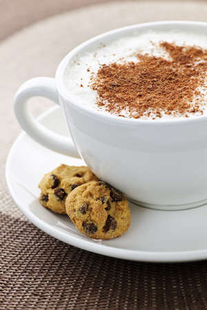 Cappuccino or latte coffee in cup with frothed milk and cookies photo
