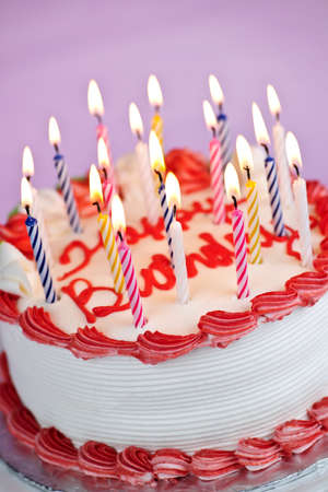 Birthday cake with burning candles and icing on pink background photo