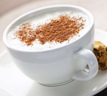 caffe: Cappuccino or latte coffee in cup with frothed milk and cookies