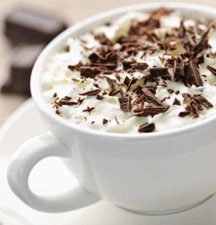 Kopje warme chocolademelk met geschoren chocolade en slag room