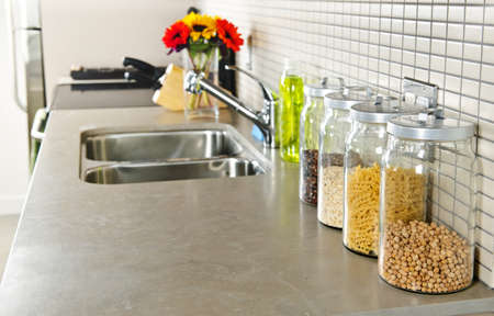 on kitchen: Modern small kitchen interior with glass jars on natural stone countertop