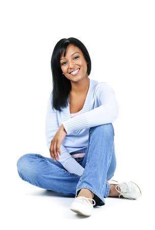 Ontspannen zwarte vrouw zitten op vloer geïsoleerd op witte achtergrond  Stockfoto
