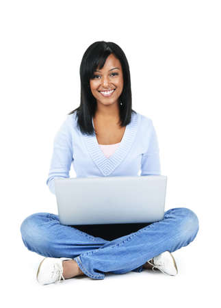 using a laptop: Happy black woman sitting with computer isolated on white background