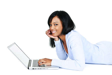 Smiling black woman using computer laying on floor looking at camera
