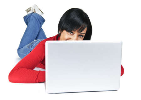 Smiling black woman peeking from behind computer laying on floor photo
