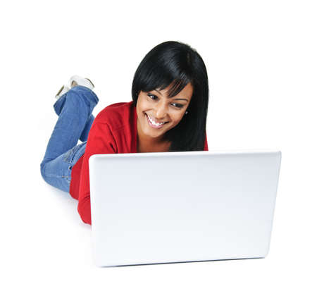 Smiling black woman typing on computer laying on floor photo