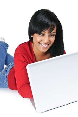 Smiling black woman typing on computer laying on floor Stock Photo - 8163238