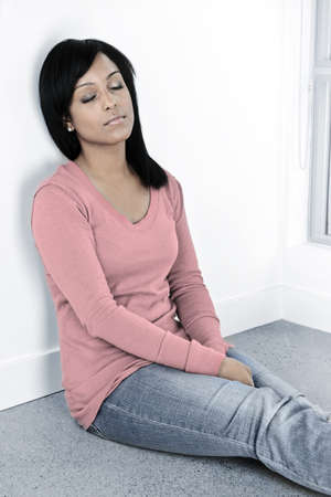 Tired black woman sitting against wall with eyes closed