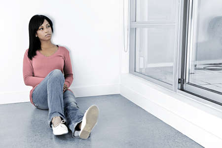 Depressed black woman sitting against wall looking out window
