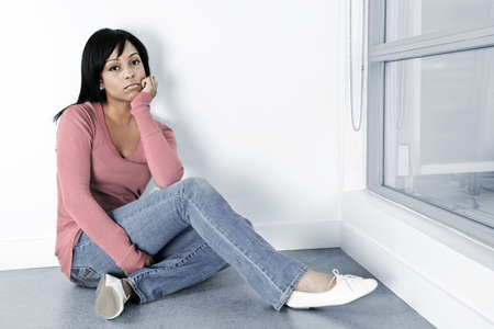 Depressed black woman sitting on the floor against wall