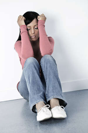 Depressed black woman sitting against wall on floor with eyes closed photo