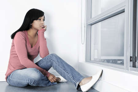 sitting on floor: Depressed black woman sitting against wall on floor looking out window