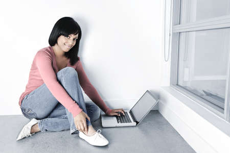 Young black woman with laptop computer sitting on floor smiling Stock Photo - 8163283