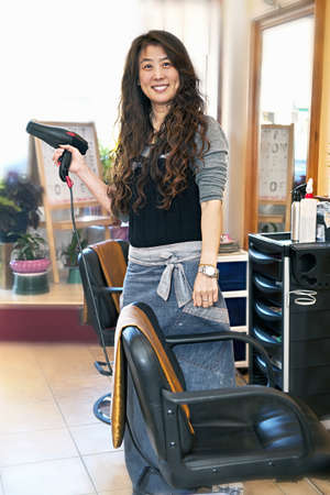 Happy hairdresser holding hairdryer in hair salon