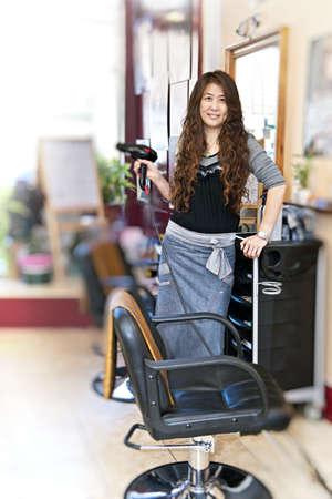 haircutting: Happy hairdresser holding hairdryer in hair salon