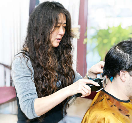 Hairdresser cutting hair in her salon with trimmer photo