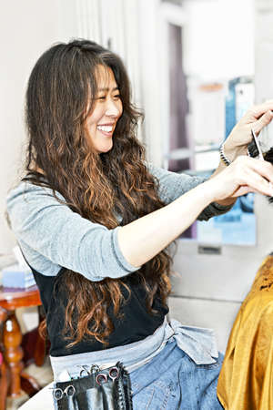 Happy hairdresser cutting hair in her salon Stock Photo - 8264792