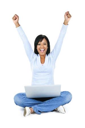 gambe aperte: Felice donna nera con le braccia sollevate e computer isolato su sfondo bianco