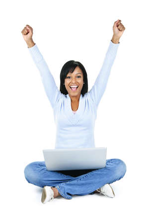 open legs: Happy black woman with arms raised and computer isolated on white background