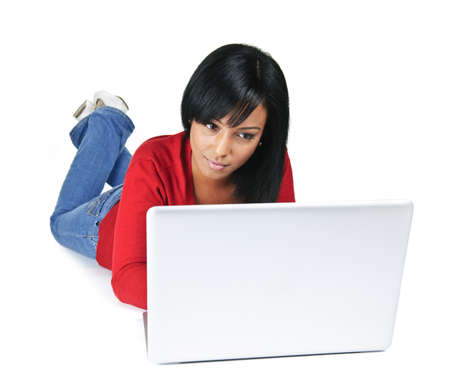 Black young woman typing on computer laying on floor Stock Photo - 8264761