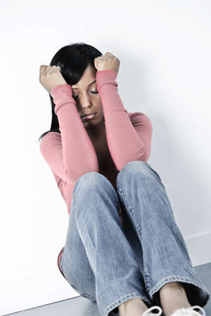 beautiful crying woman: Depressed black woman sitting against wall on floor with eyes closed