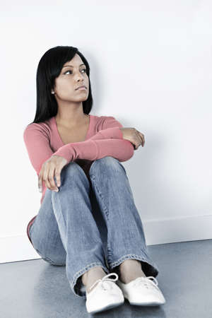 Depressed black woman sitting against wall on floor looking away photo