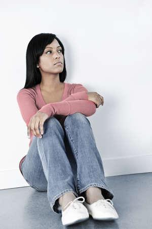 sitting floor: Depressed black woman sitting against wall on floor looking away