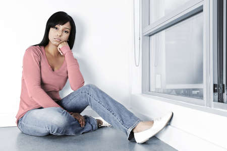 Sad young black woman sitting against wall on floor Stock Photo