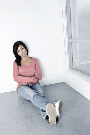 thinking woman: Depressed young black woman sitting against wall on floor