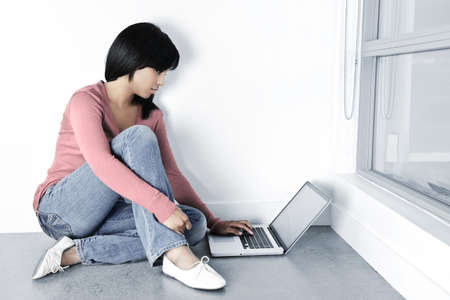 sexy young girls: Young black woman with computer sitting on floor looking at laptop Фото со стока