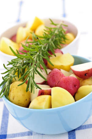 skins: Bowl of cut raw small potatoes with skins and herbs ready for roasting