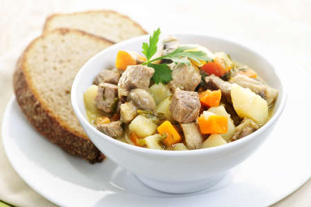 medley: Bowl of hearty beef stew with vegetables served with rye bread Stock Photo